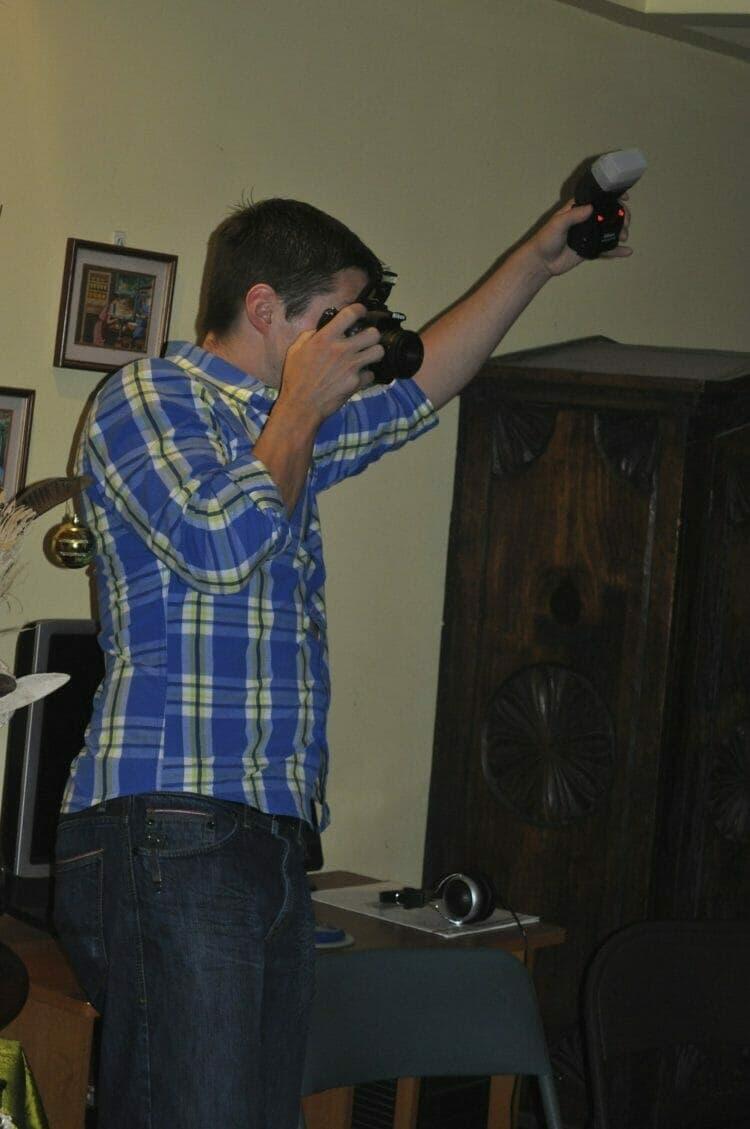 Michael Kummer holding an off camera flash