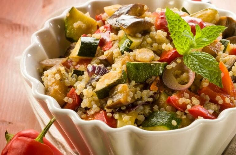 A quinoa grains bowl topped with fresh vegetables.