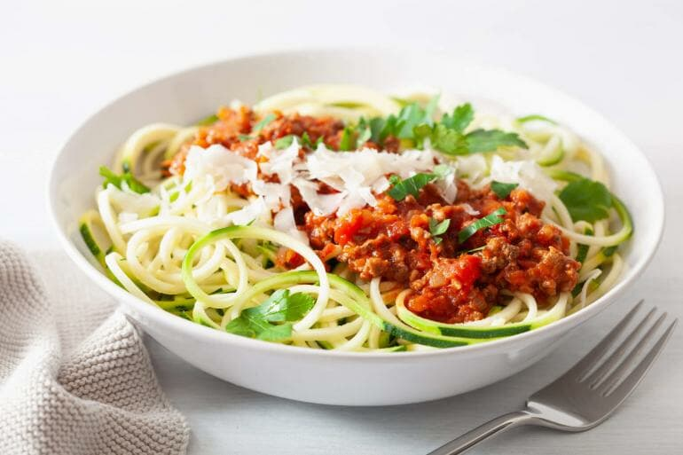 Keto paleo zoodles bolognese: zucchini noodles with meat sauce and parmesan