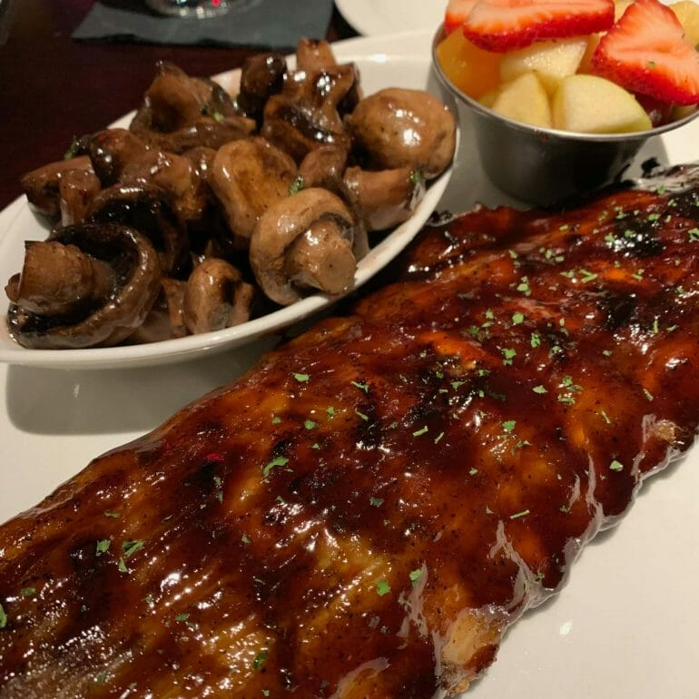 Ribs with a sauce that had way too much sugar, sautéed mushrooms and fresh fruit (Firebird Grill)