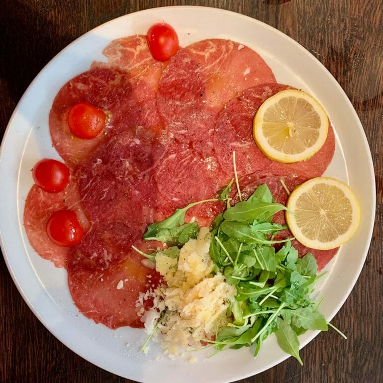 Beef carpaccio with tomatoes, parmesan and lettuce