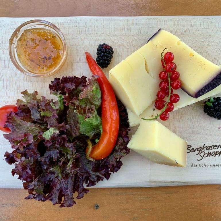 Platter of raw cheese with lettuce and jam