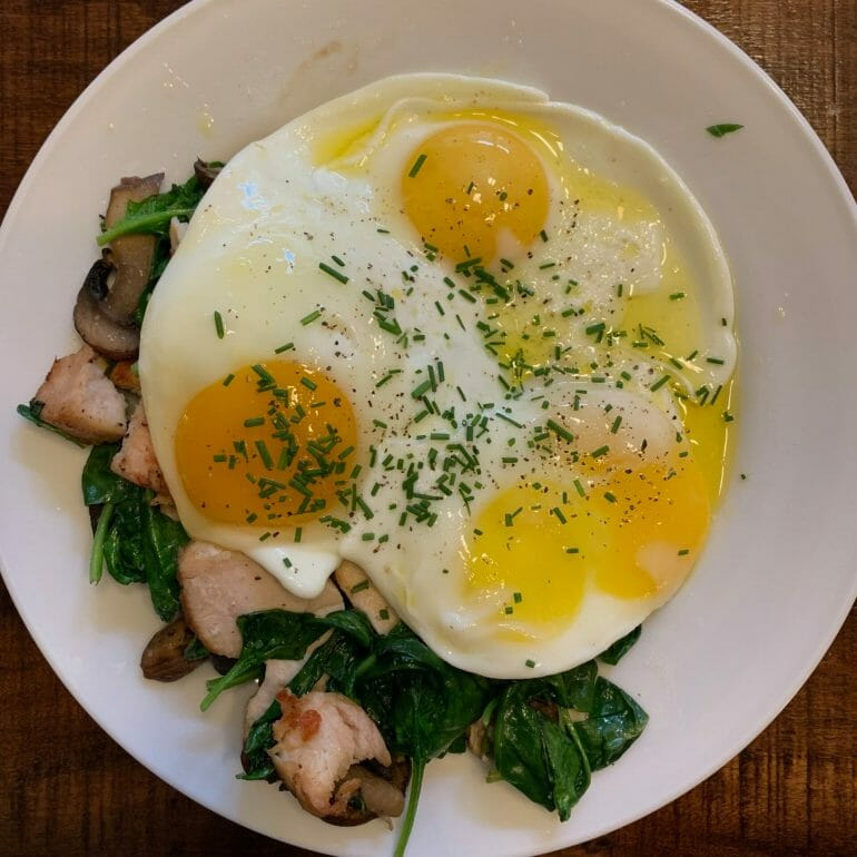 Fried eggs over grilled chicken, spinach and mushrooms