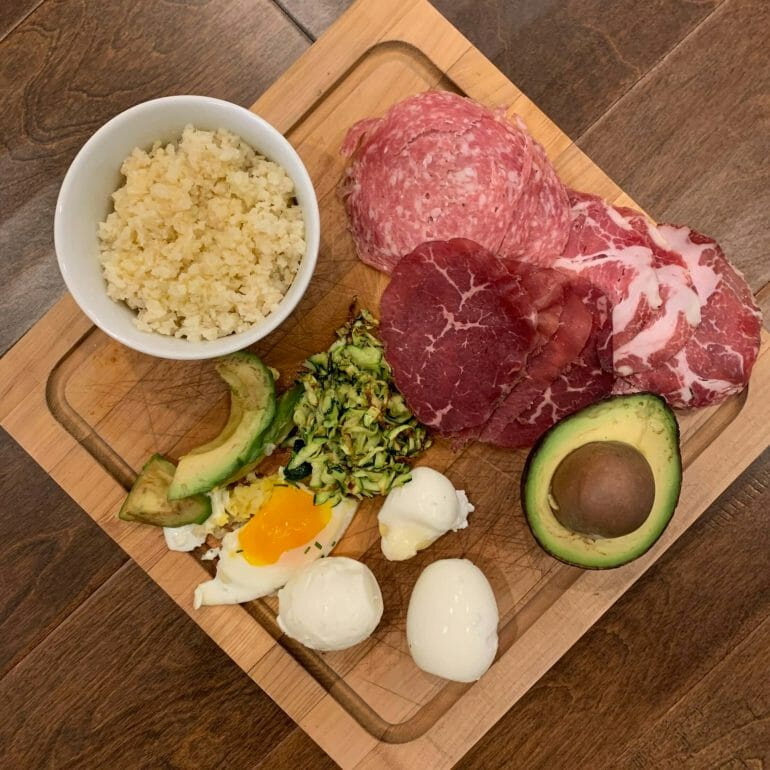 Dinner plate with riced cauliflower, uncured meats, avocado, soft-boiled eggs and riced zucchini