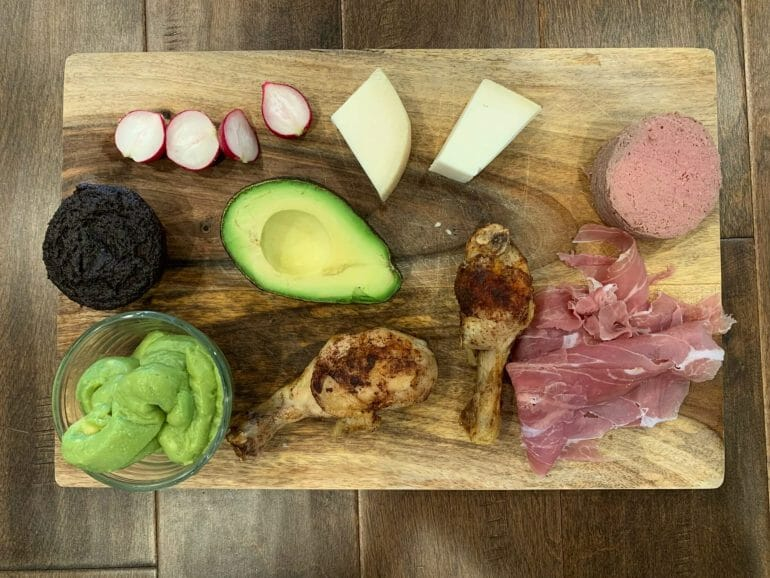 Dinner plate with uncured prosciutto, chicken thighs, avocado, liverwurst, guacamole, goat cheese, radishes and a paleo muffin