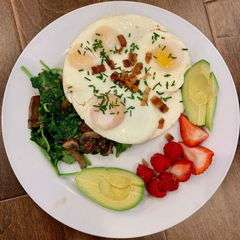 Pastured eggs with avocado, berries, spinach, mushrooms and bacon. Seasoned with chives and salt