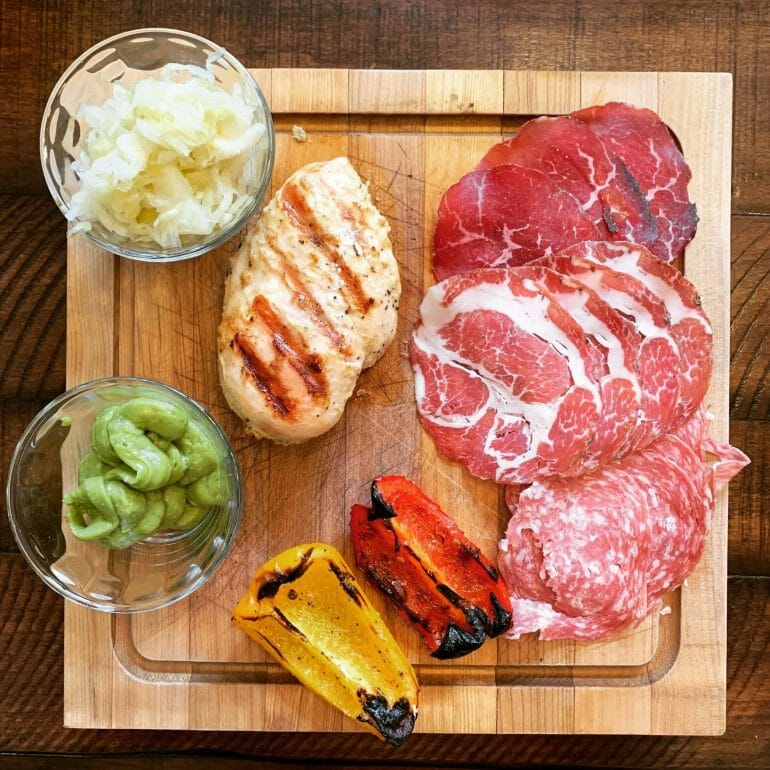 Grilled chicken with uncured cold cuts, sauerkraut, guacamole and grilled peppers