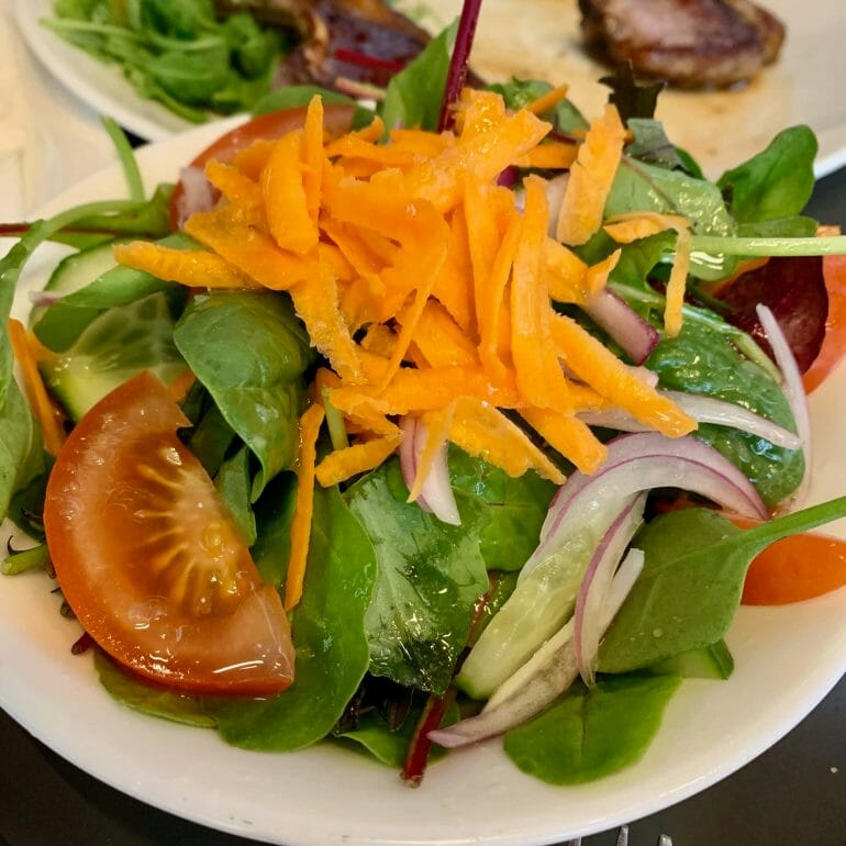 Mixed green salad with carrots, tomatoes, lettuce, cucumbers and onions