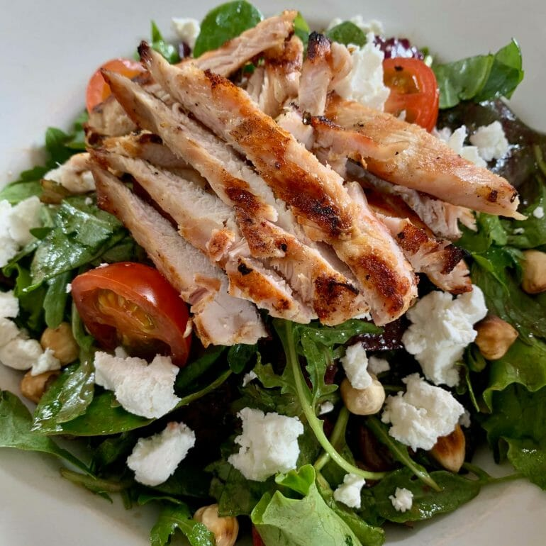 Mixed salad with grill chicken strips, goat cheese, hazelnuts, beets and tomatoes