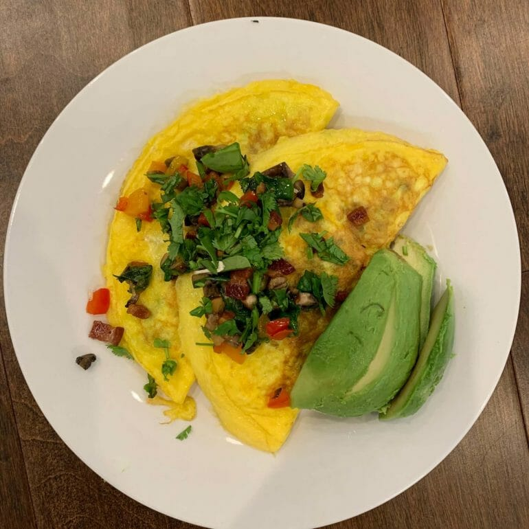 Egg omelettes filled with spinach, mushrooms and bacon. Topped with parsley, peppers and bacon. Avocado on the side