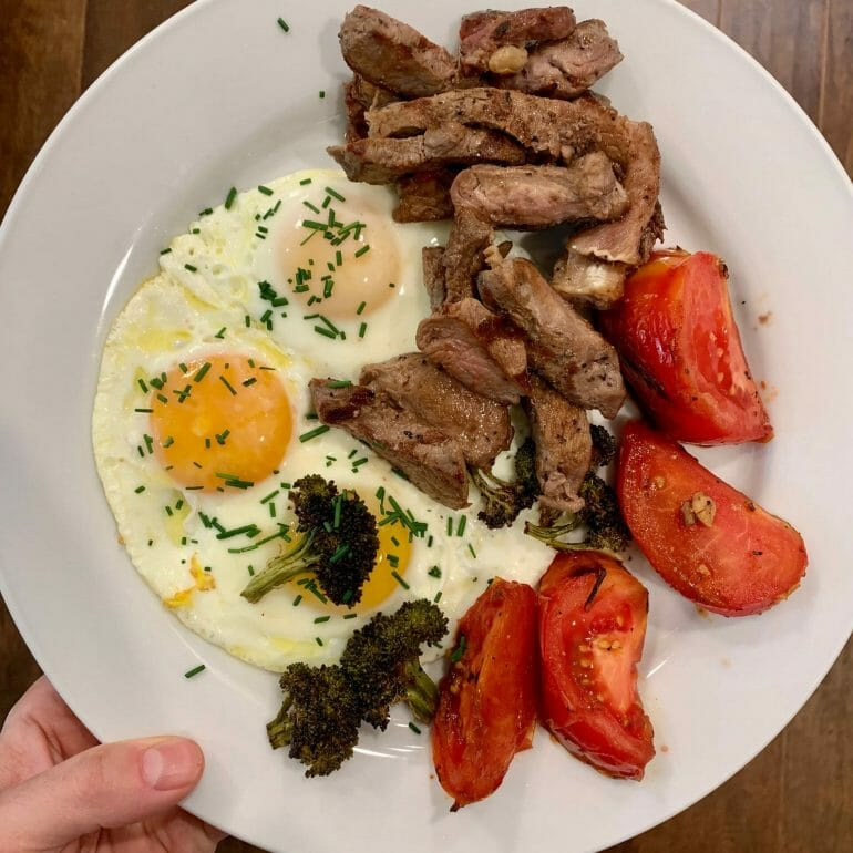 Pastured eggs with grass-fed slices of red meat, broccoli and tomatoes
