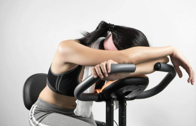 Woman exhausted and sleepy on an exercise bike