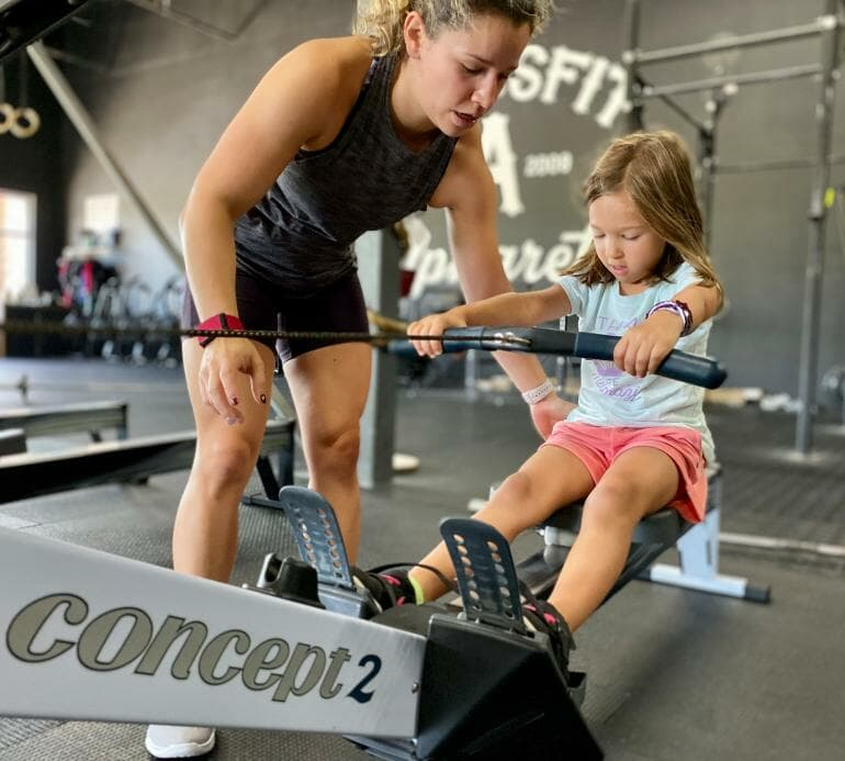 Kathy showing Isabella how to row on Concept2