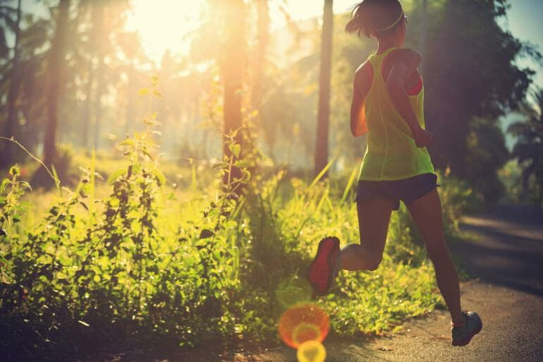 Woman running through wooded area