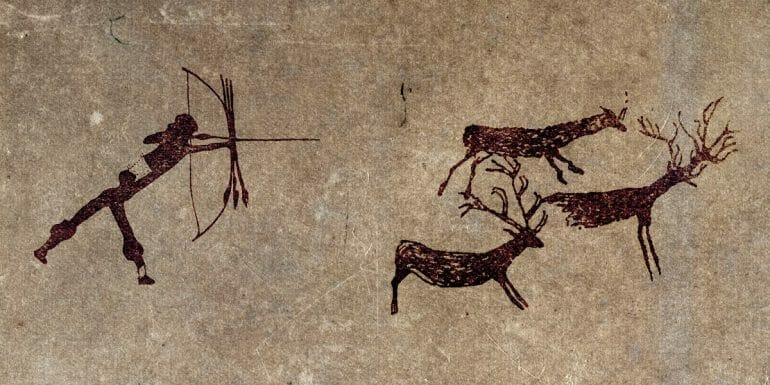 Cave drawing of human hunting animal