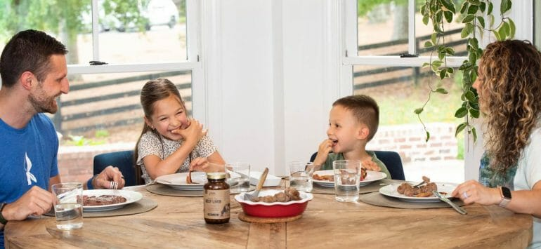 A photo showing the Kummer family happily eating together at the dinner table.