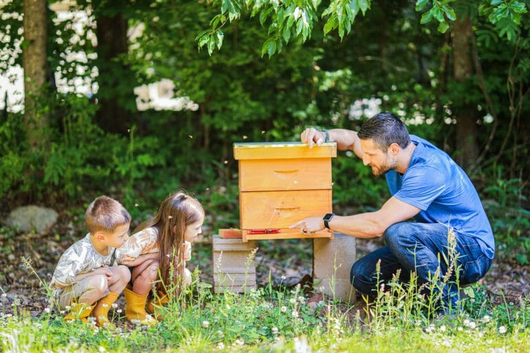 Michael Kummer with his two children and one of their beehives.