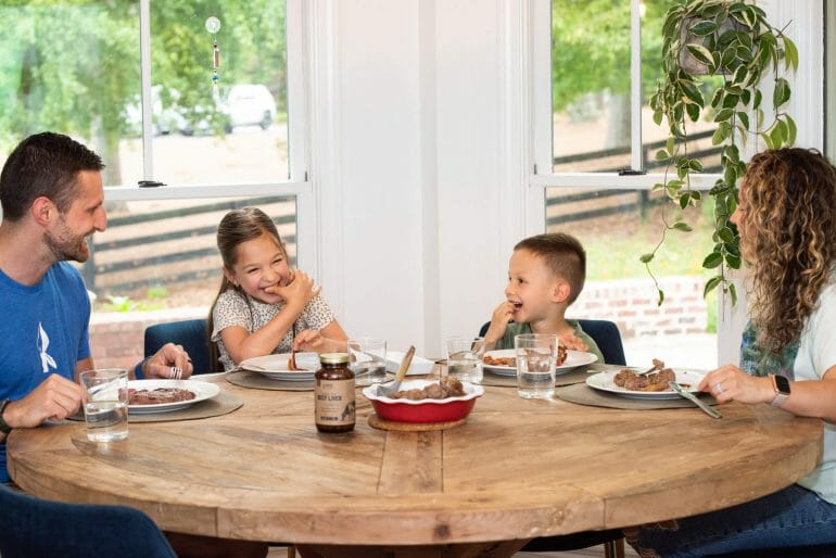 A photo of the Kummer family sitting around the table eating dinner.