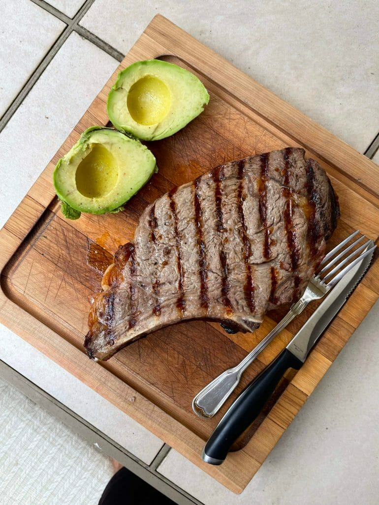 Photo of a steak and avocado with silverware on a cutting board.